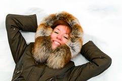 Mujer sonriente joven que se reclina sobre la nieve Fotos de archivo