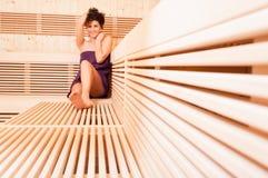 Mujer sonriente joven que se relaja en una sauna de madera Imagen de archivo