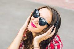 Mujer sonriente joven que se relaja y que escucha la música con los auriculares en la calle Fotos de archivo libres de regalías
