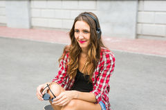 Mujer sonriente joven que se relaja y que escucha la música con los auriculares en la calle Fotografía de archivo libre de regalías