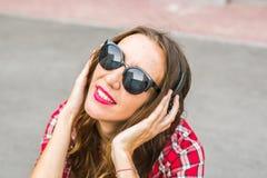Mujer sonriente joven que se relaja y que escucha la música con los auriculares en la calle Imagen de archivo libre de regalías