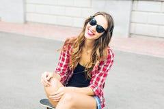 Mujer sonriente joven que se relaja y que escucha la música con los auriculares en la calle Imágenes de archivo libres de regalías