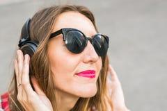 Mujer sonriente joven que se relaja y que escucha la música con los auriculares en la calle Foto de archivo libre de regalías