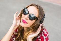 Mujer sonriente joven que se relaja y que escucha la música con los auriculares en la calle Imagenes de archivo