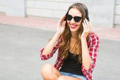Mujer sonriente joven que se relaja y que escucha la música con los auriculares en la calle Fotos de archivo