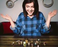Mujer sonriente joven que se sienta delante de los anillos en una tabla Imagen de archivo