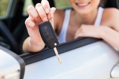 Mujer sonriente joven que se sienta en el coche que toma llave foto de archivo