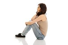 Mujer sonriente joven que se sienta en el piso Foto de archivo
