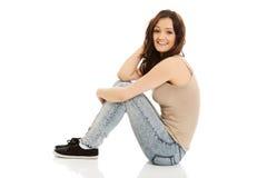 Mujer sonriente joven que se sienta en el piso Fotos de archivo