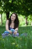 Mujer sonriente joven que se sienta en la hierba Fotografía de archivo