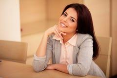 Mujer sonriente joven que se sienta en la tabla Imagenes de archivo
