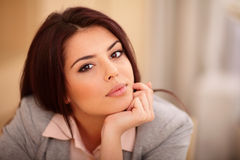 Mujer sonriente joven que se sienta en la tabla Imagen de archivo libre de regalías