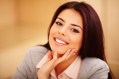 Mujer sonriente joven que se sienta en la tabla Foto de archivo