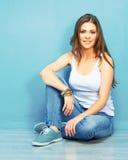 Mujer sonriente joven que se sienta en piso contra la pared azul Imágenes de archivo libres de regalías