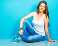 Mujer sonriente joven que se sienta en piso contra la pared azul Imagen de archivo
