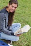 Mujer sonriente joven que se sienta a piernas cruzadas en un parque Foto de archivo