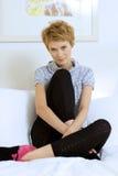 Mujer sonriente joven que se sienta a piernas cruzadas en un sofá Fotografía de archivo libre de regalías
