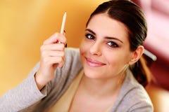 mujer sonriente joven que sostiene el lápiz Imagen de archivo
