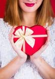 Mujer sonriente joven que sostiene la caja de regalo roja en la forma del corazón en el re foto de archivo