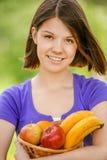 Mujer sonriente joven que sostiene la cesta con las frutas Imagen de archivo