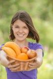 Mujer sonriente joven que sostiene la cesta con las frutas Foto de archivo
