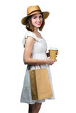 Mujer sonriente joven que sostiene un bolso de compras y una taza de papel Fotos de archivo