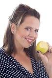 Mujer sonriente joven que sostiene una manzana Imagenes de archivo