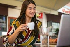 Mujer sonriente joven que sostiene una taza de café y que mira somethi Imágenes de archivo libres de regalías