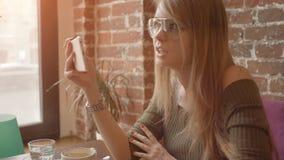 Mujer sonriente joven que tiene conversación video usando smartphone durante el desayuno en cafetería, metrajes