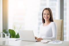 Mujer sonriente joven que trabaja con el ordenador portátil foto de archivo libre de regalías
