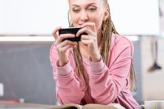 Mujer sonriente joven que usa el teléfono móvil en casa Fotos de archivo libres de regalías
