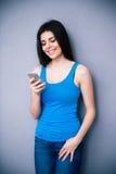 Mujer sonriente joven que usa smartphone Foto de archivo
