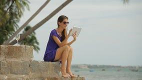 Mujer sonriente joven que usa una tableta en la playa almacen de metraje de vídeo