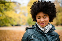 Mujer sonriente joven tímida en parque del otoño Imagenes de archivo