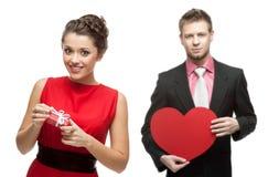 Mujer sonriente joven y hombre hermoso que llevan a cabo el corazón rojo en blanco Fotografía de archivo libre de regalías