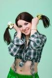 Mujer sonriente linda divertida con las coletas en verde Fotos de archivo libres de regalías