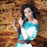 Mujer sonriente linda joven con el peinado de los dreadlocks, vestido en vestido azul y pendientes azules del dreamcatcher con la Fotos de archivo libres de regalías
