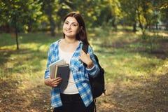 Mujer sonriente linda joven del estudiante con la mochila y el suplente de los libros Imagen de archivo libre de regalías