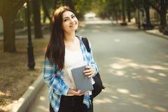 Mujer sonriente linda joven del estudiante con la mochila y el suplente de los libros Fotografía de archivo libre de regalías