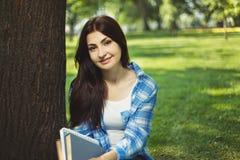 Mujer sonriente linda joven del estudiante que se sienta en el parque con los libros Fotos de archivo libres de regalías