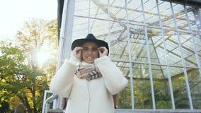 Mujer sonriente linda que lleva las gafas de sol elegantes y que mira derecho a la cámara en el parque de la ciudad almacen de metraje de vídeo
