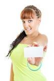 Mujer sonriente linda que muestra la muestra en blanco vacía de la tarjeta de papel con la copia Fotografía de archivo