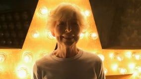 Mujer sonriente mayor que se opone a la iluminación almacen de video