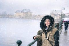 Mujer sonriente mientras que nieva Imagen de archivo libre de regalías