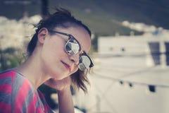 Mujer sonriente moderna joven con las gafas de sol y la expresión casual Fotos de archivo