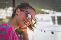 Mujer sonriente moderna joven con las gafas de sol y la expresión casual Fotos de archivo libres de regalías