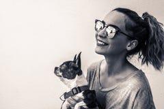 Mujer sonriente moderna joven con su perro en una actitud casual Fotos de archivo