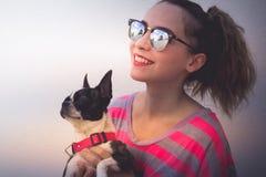Mujer sonriente moderna joven con su perro en una actitud casual Foto de archivo libre de regalías