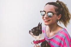 Mujer sonriente moderna joven con su perro en una actitud casual Imagen de archivo