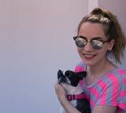 Mujer sonriente moderna joven con su perro en una actitud casual Imagen de archivo libre de regalías